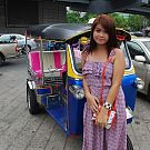 Lovely Thai woman poses beside tuktuk transporter before taking ride to hotel room
